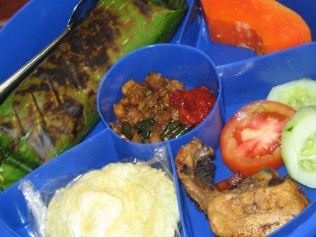 Paket seharga Rp. 8,000,- Terdiri dari Nasi Bakar (Nasi Lemak/Gurih dengan isian Oseng Daging Ayam), Lauk: Ayam Goreng Baceman, Sayur: Oseng Tempe Lombok Ijo dan Lalapan, Buah: Pepaya, Sambal dan Emping.